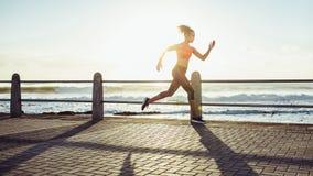 Femme sprintant pendant le coucher du soleil images stock
