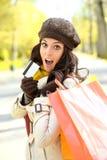Femme stupéfaite avec les paniers et la carte de crédit Photographie stock libre de droits