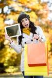 Femme stupéfaite tenant les paniers et le comprimé en automne Photos libres de droits