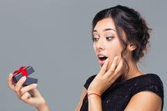 Femme stupéfaite tenant le boîte-cadeau Photographie stock libre de droits