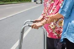 Femme supérieure à l'aide d'une rue de croix de marcheur Photos stock