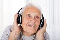 Femme supérieure à l'aide de l'écouteur à la maison Images libres de droits