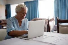 Femme supérieure à l'aide de l'ordinateur portable tout en se reposant dans la maison de repos Photos stock