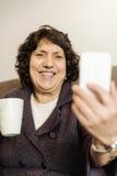 Femme supérieure à l'aide de son téléphone portable Photographie stock libre de droits