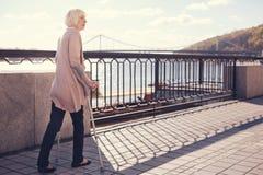 Femme supérieure à l'aide des béquilles pour marcher le long du pont Images stock