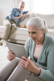 Femme supérieure à l'aide du comprimé numérique tandis que son mari jouant des échecs sur le sofa Photo stock