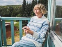 Femme supérieure à l'aide du téléphone intelligent dehors Photo stock