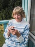 Femme supérieure à l'aide du téléphone intelligent dehors Photos stock