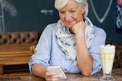 Femme supérieure à l'aide du téléphone intelligent tout en se reposant à la table en café Images stock