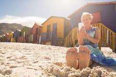 Femme supérieure à l'aide du téléphone intelligent tout en se reposant sur le sable contre des huttes Photos libres de droits