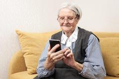 Femme supérieure à l'aide du téléphone portable Photo stock
