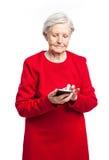 Femme supérieure à l'aide du téléphone portable au-dessus du blanc Image stock