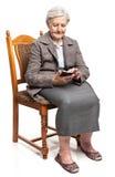 Femme supérieure à l'aide du téléphone portable se reposant sur la chaise Image libre de droits