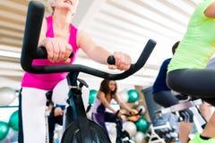 Femme supérieure à la forme physique tournant sur le vélo dans le gymnase Photographie stock libre de droits