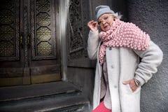 Femme supérieure à la mode sûre posant près de la porte antique Images libres de droits
