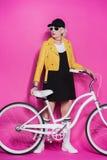 Femme supérieure à la mode utilisant la veste en cuir jaune se tenant avec la bicyclette Images libres de droits
