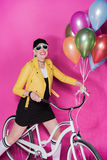 Femme supérieure à la mode utilisant la veste en cuir jaune se tenant avec la bicyclette et les ballons colorés Photographie stock