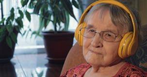 Femme supérieure écoutant la musique dans des écouteurs banque de vidéos