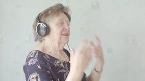 Femme supérieure écoutant la musique sur des écouteurs banque de vidéos