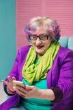 Femme supérieure élégante à l'aide du téléphone intelligent avec surprise Photo libre de droits