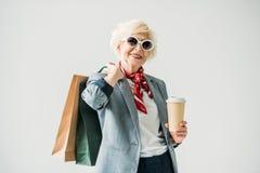 femme supérieure élégante dans la veste et des lunettes de soleil avec les paniers et le café, Image stock