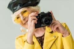 femme supérieure élégante dans le béret de guêpe et de cuir prenant la photo sur l'appareil-photo, Images stock