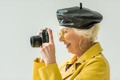 femme supérieure élégante dans le béret de guêpe et de cuir prenant la photo sur l'appareil-photo, Images libres de droits