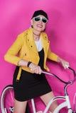 Femme supérieure élégante heureuse utilisant la veste en cuir jaune se tenant avec la bicyclette Image libre de droits