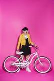 Femme supérieure élégante utilisant la robe noire et la veste en cuir jaune se tenant avec la bicyclette Photo libre de droits
