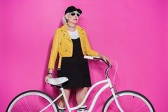 Femme supérieure élégante utilisant la veste en cuir jaune et les lunettes de soleil se tenant avec la bicyclette Image stock