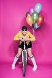 Femme supérieure élégante utilisant la veste en cuir jaune se tenant avec la bicyclette et les ballons colorés Image stock