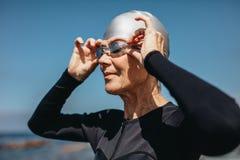 Femme supérieure étant prête pour nager en mer photographie stock libre de droits