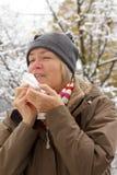 Femme supérieure éternuant dehors hiver Photos stock