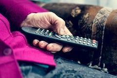 Femme supérieure actionnant la TV Images stock