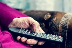 Femme supérieure actionnant la TV Image libre de droits