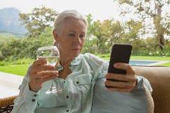 Femme supérieure active à l'aide du téléphone portable ayant le champagne dans le porche images stock