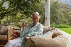 Femme supérieure active ayant le champagne dans le porche à la maison photographie stock libre de droits