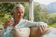 Femme supérieure active ayant le champagne dans le porche à la maison photos stock