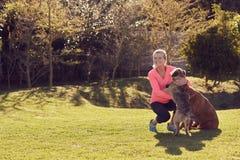 Femme supérieure active choyant ses chiens dehors dans un jardin Photos libres de droits