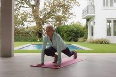 Femme supérieure active faisant le yoga sur le tapis d'exercice dans le porche à la maison photos libres de droits