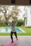 Femme supérieure active faisant le yoga sur le tapis d'exercice dans le porche à la maison photographie stock libre de droits