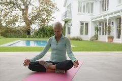 Femme supérieure active faisant le yoga sur le tapis d'exercice dans le porche à la maison image stock