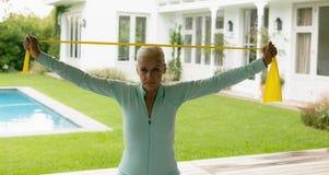 Femme supérieure active s'exerçant avec la bande de résistance en porche à la maison photographie stock libre de droits