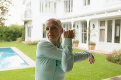 Femme supérieure active s'exerçant en porche à la maison photos libres de droits