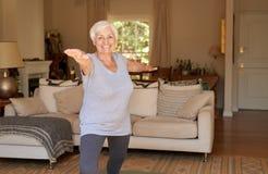 Femme supérieure active souriant et faisant seul le yoga à la maison Images stock
