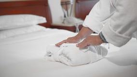 Femme supérieure adulte non reconnue mettant le peignoir blanc sur un lit dans une chambre d'hôtel Mouvement lent, plan rapproch? clips vidéos