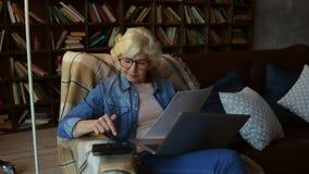 Femme supérieure agréable effectuant des calculs pour fixer sa planification financière banque de vidéos