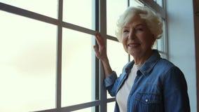 Femme supérieure agréable satisfaite tenant la fenêtre proche clips vidéos