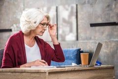 Femme supérieure ajustant des lunettes Photos libres de droits