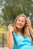 Femme supérieure amicale heureuse sur l'oscillation extérieure Photo stock